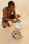 Shucking oysters on Bureh Beach,Sierra Leone