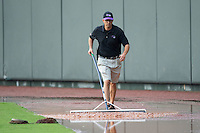A Winston-Salem Dash staff member uses a roller to try and remove water from the warning track in the outfield prior to the game against the Myrtle Beach Pelicans at BB&T Ballpark on July 7, 2016 in Winston-Salem, North Carolina.  The Dash defeated the Pelicans 13-9.  (Brian Westerholt/Four Seam Images)