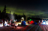 Aliy Zirkle, Joar Leifseth Ulsom and Richie Diehl cook for their team under the glow of the Aurora in the early morning at the Finger Lake checkpoint on Monday, March 4, 2019 during the 2019 Iditarod.<br /> <br /> Photo by Jeff Schultz/  (C) 2019  ALL RIGHTS RESERVED