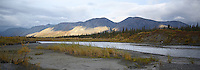 The setting sun briefly illuminates the Brooks Range along the Sheenjek River, in Alaska's Arctic National Wildlife Refuge in late August. STITCHED PANORAMA