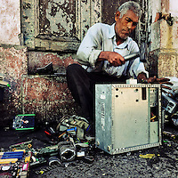 A Salvadoran recycler dismantles an old desktop computer to obtain valuable components and metals on the street of San Salvador, El Salvador, 14 November 2016.