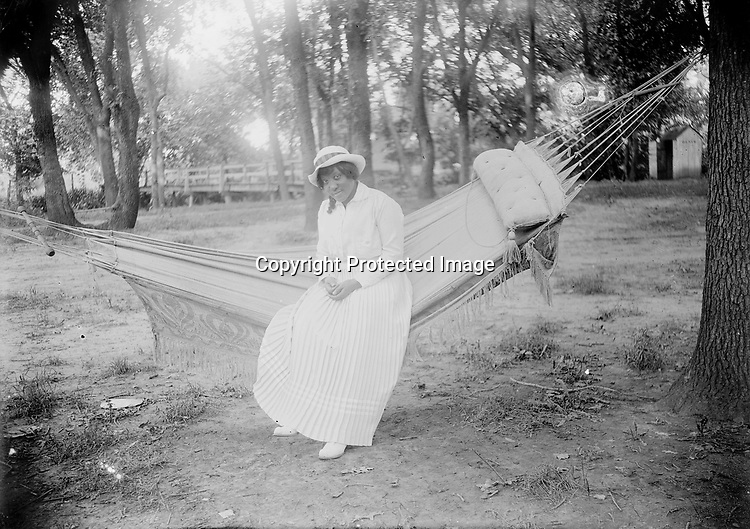 LADY ON A HAMMOCK. A tasseled hammock with built-in pillow provides a perch for this lady to display her elaborately pleated skirt. The footbridge in the background suggests this scene may be Epworth Park, a Methodist-affiliated park and revival ground south of Lincoln on Salt Creek.<br /> <br /> Photographs taken on black and white glass negatives by African American photographer(s) John Johnson and Earl McWilliams from 1910 to 1925 in Lincoln, Nebraska. Douglas Keister has 280 5x7 glass negatives taken by these photographers. Larger scans available on request.