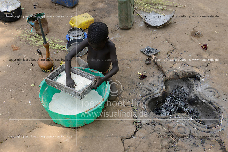 ETHIOPIA Gambela, village of Anuak tribe, boy sieve flour at cooking place / AETHIOPIEN Gambela, Dorf der Anuak Volksgruppe, Junge siebt Mehl an Kochstelle