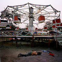 A boy sleeps on the sand near a funfair on the Ilha de Luanda..