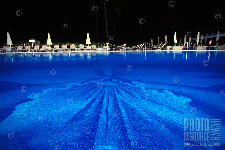 A view of Halekulani hotel's swimming pool in Waikiki at night.  The bottom is tiled with an orchid design