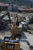 Switzerland. Canton Graubunden. Bregaglia valley. Bondo. A second massive landslide hit Bondo while the remote village was still recovering from a huge landslide caused by a giant rockslide swept down from Piz Cengalo on August 23, 2017. The mudslide smashed the carpentry factory and equipment that was being used to clear debris from the previous landslide. Men at work with excavators to pull out the truck from the mudslide. 26.08.2017 © 2017 Didier Ruef