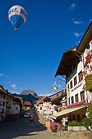 Hot air balloon passing over La Gruyère's main street