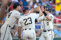Michigan Wolverines catcher Joe Donovan (0) celebrates with head coach Erik Bakich (23) and teammate Jack Bredeson (34) against the Vanderbilt Commodores during Game 1 of the NCAA College World Series Finals on June 24, 2019 at TD Ameritrade Park in Omaha, Nebraska. Michigan defeated Vanderbilt 7-4. (Andrew Woolley/Four Seam Images)