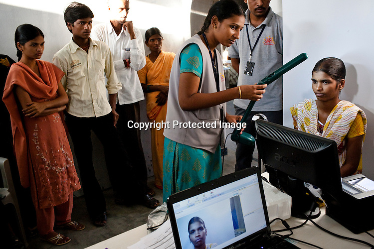 An official assists a young woman to have her photo taken as part of the enrollment that is on its way in Naagaaram village, outskirts of Hyderabad in Andhra Pradesh, India. India is assigning each one of its 1.2 billion people a unique ID number based on digital finger prints and iris scan. Photograph: Sanjit Das/Panos