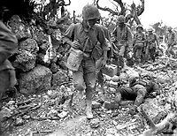Marines pass through a small village where Japanese soldiers lay dead.  Okinawa, April 1945.  Norris G. McElroy.  (Marine Corps)<br /> Exact Date Shot Unknown<br /> NARA FILE #:  127-N-95-119485<br /> WAR & CONFLICT BOOK #:  1231