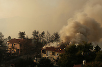 Pictured: A house is burning in the village of Kalamos.<br /> Re: A forest fire has been raging in the area of Kalamos, 20 miles east of Athens in Greece. There have been power cuts, country houses burned and children camps evacuated from the area.