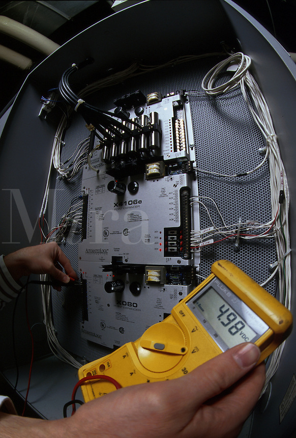 Technician checking the readings of a monitoring control computer of a heating air conditioning unit.