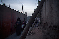 Uighurs move past a partially demolished house in the Old City of Kashgar, Xinjiang, China.