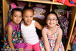 Preschool ages 3-5 portrait of three girls sitting in cubbies happy smiling horizontal