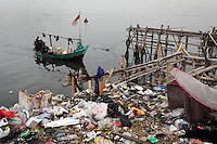 A fishing boat comes into the port area of northern Jakarta. The bay has become heavily polluted as a result of run-off from the nearby city.