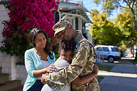 Off duty male US military soldier at home with his wife and daughter. For sale as stock photography, DOD compliant.