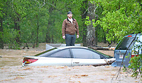 Jaxon Douglass, 21, waits patiently for water rescue personnel to reach him as he stands on concrete blocks outside his grandparents' home on Rustic Drive Wednesday morning. His uncle was swept away in the water and was also rescued safely.<br /> (Pea Ridge Times/Annette Beard)