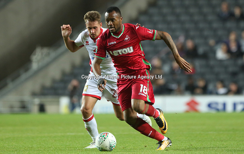 Jordan Ayew of Swansea City is challenged by Callum Brittain of MK Dons during the Carabao Cup Second Round match between MK Dons and Swansea City at StadiumMK, Milton Keynes, England, UK. 22 August 2017