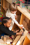 Education preschool 2-4 year olds block area boy and girl playing together using blocks as ramps vertical