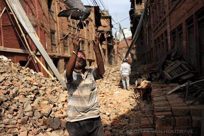 A resident pauses from cleaning up the earthquake damage to release a pigeon which was disoriented amidst loose ruble in a heavily devastated neighbor of Bhaktapur, Kathmandu Valley, Nepal in June 2015. Painstaking cleanup was underway with many residents are using their own hands and simple tools to stabilize their homes before the arrival of heavy monsoon rains.
