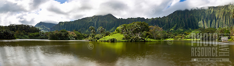 A peaceful day along a lake, with the Ko'olau mountains in the distance, Kane'ohe, Windward O'ahu.