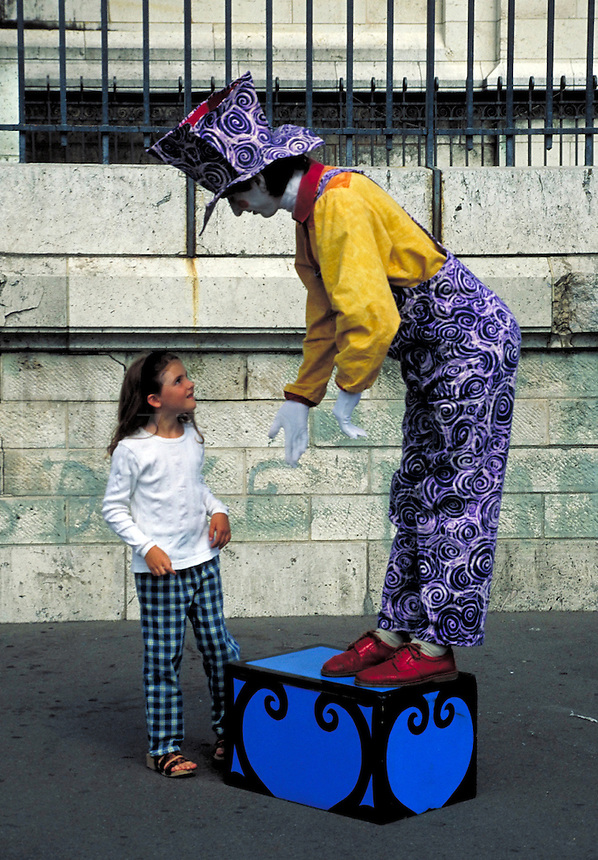 Whiteface mime in tall hat stands on box and gestures for bewildered girl to step up with him. Paris, France.