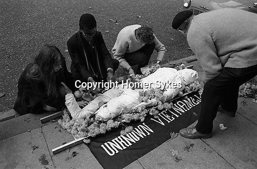 Demonstrators with effigy of an unknown Vietnamese's covered in bandages and surrounded with flowers. Anti Vietnam War demonstration in  Grosvenor Square outside the American Embassy London 1968