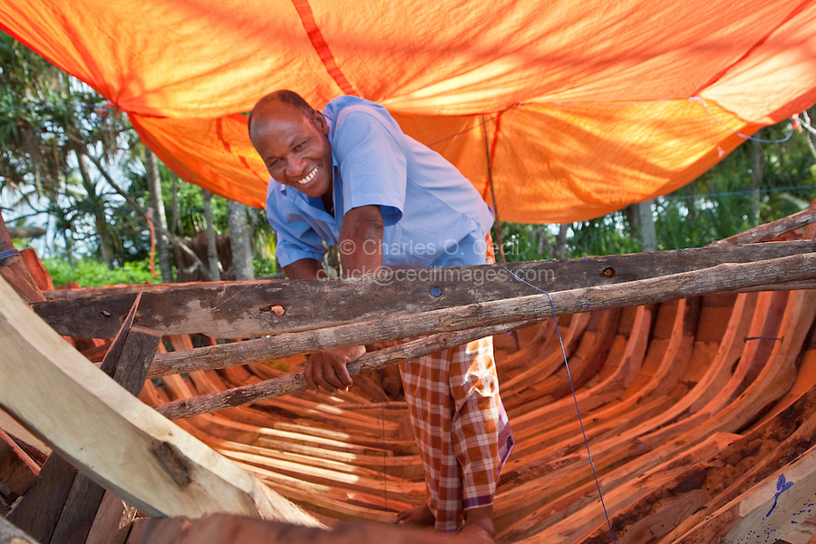 Nungwi, Zanzibar, Tanzania.  Dhow Construction.  Internal ribs in place to support the planks of the hull.  The man is wearing a kikoi, the wrap-around skirt worn by many Zanzibari men.