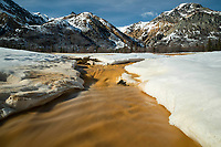 Spring landscape of iron-colored water coming from Sheep Mountain and running through spring snow.  Talkeetna Mountains.  Alaska   Sunny day-- blue sky<br /> <br /> Photo by Jeff Schultz/  (C) 2020  ALL RIGHTS RESERVED