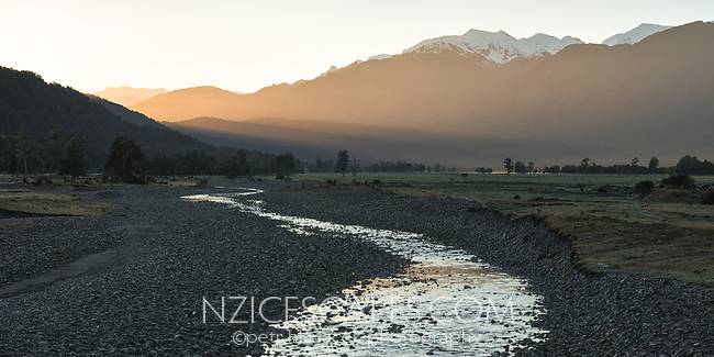 Farmland in Fox Glacier with creek and Southern Alps at sunrise, Westland Tai Poutini National Park, UNESCO World Heritage Area, West Coast, New Zealand, NZ