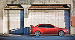 Grunge effect applied to a photo of a 2009 Mitsubishi Lancer Evolution MR in front of an old warehouse garage door.