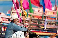 Man eating while sitting in front of the colorful boats and flags of the Yamuna River, during Holi celebrations in Mathura Uttar Pradesh India