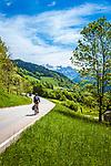 Deutschland, Bayern, Berchtesgadener Land, Ramsau bei Berchtesgaden: Radfahrer unterwegs auf der B305 Richtung Ramsau, im Hintergrund das Hagengebirge, ein Gebirgsstock der Berchtesgadener Alpen | Germany, Upper Bavaria, Berchtesgadener Land; Ramsau bei Berchtesgaden: cyclist on road B305 to Ramsau, at background Hagen Mountains, a subrange of the Berchtesgaden Alps