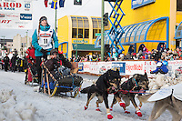 Kristy Berington and team leave the ceremonial start line with an Iditarider at 4th Avenue and D street in downtown Anchorage, Alaska during the 2015 Iditarod race. Photo by Jim Kohl/IditarodPhotos.com