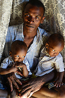 MADAGASCAR, Mananjary, tribe ANTAMBAHOAKA, fady, according to the rules of their ancestors twin children are a taboo and not accepted in the society, fishing village ANILAVINARY, father with his twin children / MADAGASKAR, Zwillinge sind ein Fady oder Tabu beim Stamm der ANTAMBAHOAKA in der Region Mananjary, Fischerdorf ANILAVINARY, Herr PARTIAL BEMANANTSOA mit Zwillingen MARIOCE VELONALY BEMANANTSOA und MARIO VELONALY BEMANANTSOA