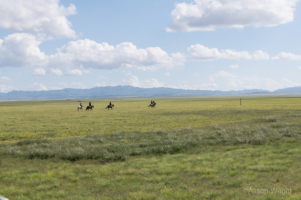 Mongolia, Gobi Gurvan Saikhan National Park, Gobi Desert, Three Camel Lodge. Men on horses. .