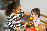 preschool 3-4 year olds pretend play two girls making telephone calls one subsituting a camera for a telephone