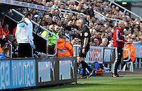 Pictured: Referee Chris Foy gets off the pitch after getting knocked over earlier by a deflection. Saturday 19 April 2014<br /> Re: Barclay's Premier League, Newcastle United v Swansea City FC at St James Park, Newcastle, UK.