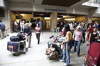 Tourists with suitcases on luggage carts at the International Arrivals area of the Honolulu International Airport