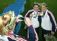 26 August 2004:  Cindy Parlow takes a photo of Mia Hamm and Kristine Lilly showing off their gold medals after defeating Brazil, 2-1 in overtime at Karaiskakis Stadium in Athens, Greece.  Credit: Michael Pimentel / ISI.