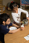 Preschool 4 year olds girl pouring milk for friend