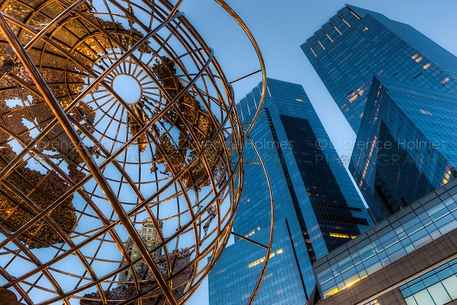 The stainless steel globe outside of the Trump International Hotel and Tower contrasts with the twin towers of the Time Warner Center across Columbus Circle, in the last hour before sunrise in New York City.  The globe was created by artist Kim Brandell.
