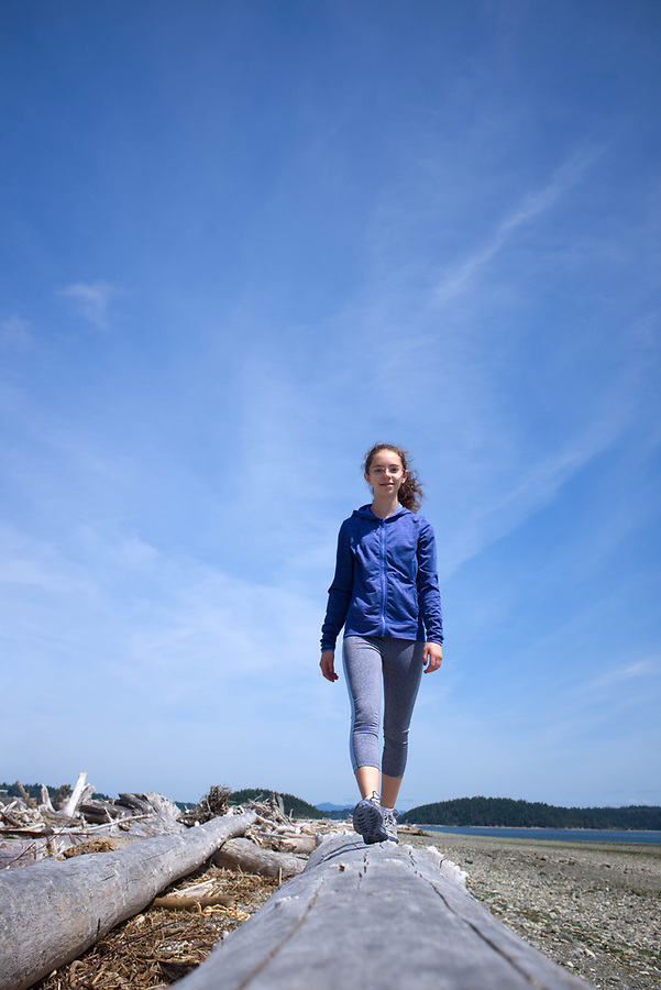 Teen-age girl balancing on beach log, Ala Spit County Park, Oak Harbor, Whidbey Island, Island County, Washington State, USA