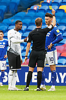 Referee John Brooks (C) shows a yellow card to both Marc Guehi of Swansea City and Kieffer Moore of Cardiff City (R) during the Sky Bet Championship match between Cardiff City and Swansea City at the Cardiff City Stadium, Cardiff, Wales, UK. Saturday 12 December 2020