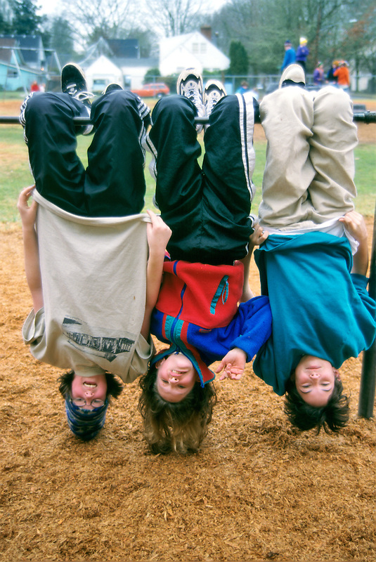 Fifth grade students swinging on bars on playground. Corvallis, Oregon