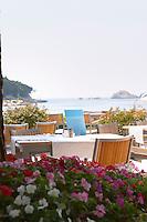 Restaurant outside seating terrace. View over the sea. Hotel and restaurant Kompas. Uvala Sumartin bay between Babin Kuk and Lapad peninsulas. Dubrovnik, new city. Dalmatian Coast, Croatia, Europe.