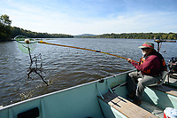 Mike McMullin, of Fayetteville, an Arkansas Master Naturalist, uses a net Saturday, Oct. 9, 2021, to pull a trotline from Lake Sequoyah while taking part in the annual fall cleanup of the lake in Fayetteville. The event is organized by the Beaver Watershed Alliance and the city of Fayetteville's Parks and Recreation Department, Boston Mountain Solid Waste District and Keep Arkansas Beautiful. Visit nwaonline.com/211010Daily/ for today's photo gallery.<br /> (NWA Democrat-Gazette/Andy Shupe)