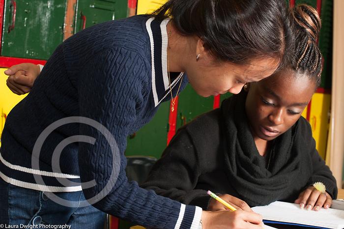 Education high school female teacher working with female student on mathematics problem