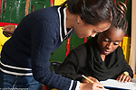 Education high school female teacher working with female student on mathematics problem