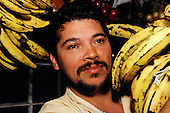 San Jose, Costa Rica. Market vendor with bunches of ripe yellow bananas.